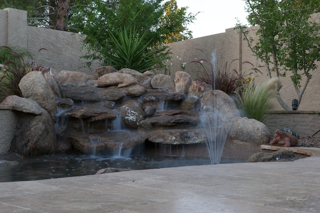 A pool remodel with Glendale landscaping can change your whole backyard like this pool deck waterfall pond did on this project.